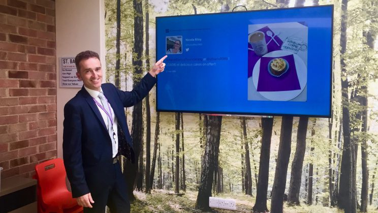 A picture of St Bartholomew's Primary Academy, Swindon, Wiltshire and also accredited, Apple Regional Training Centre, showcasing their TrilbyTV digital signage with Headteacher Dan Oakes