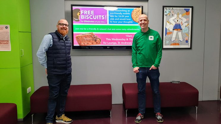 Neil Emery and Carl Bayliss standing in front of a digital signage screen showcasing free biscuits